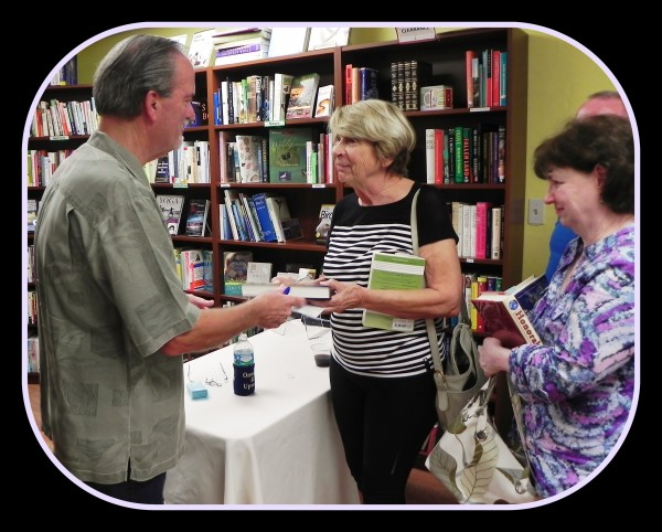 Macomber personalizing purchased novels by enthusiastic readers at Copperfish Books in Punta Gorda, FL [December 2015]
