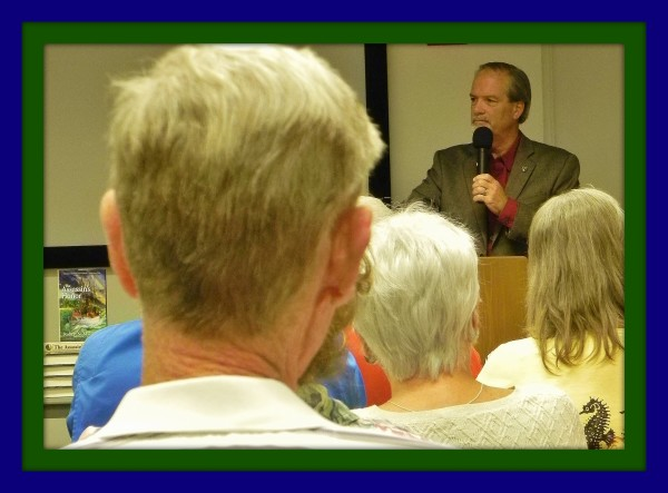 """Author & lecturer, Robert N. Macomber speaks to a full house at the Bonita Springs Library [Florida] on his subject """"Sanibel And Captiva Islands In The Civil War"""" with his 12th novel, The Assassin's Honor displayed."""