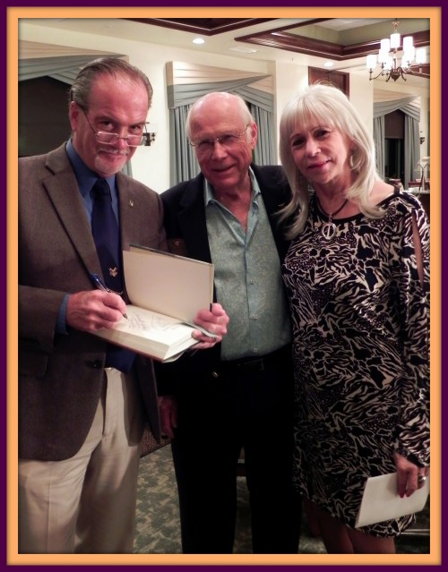 Author & historical lecturer, Robert N. Macomber signs a copy of his latest novel after giving a talk at the Military Officers Association [MOASWF] dinner meeting in Naples, organized by Bill Hodges [middle].
