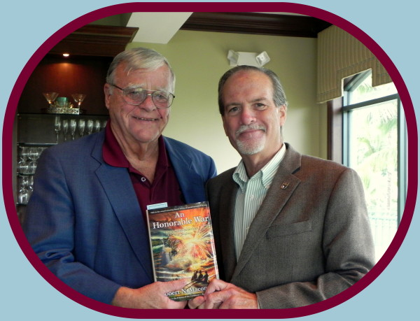 Robert Hoffman (left) excited to finally have the newest novel, An Honorable War, by author and historian Robert N. Macomber at the Reserve Officers Association [ROA] meeeting of Naples/Marco Island.