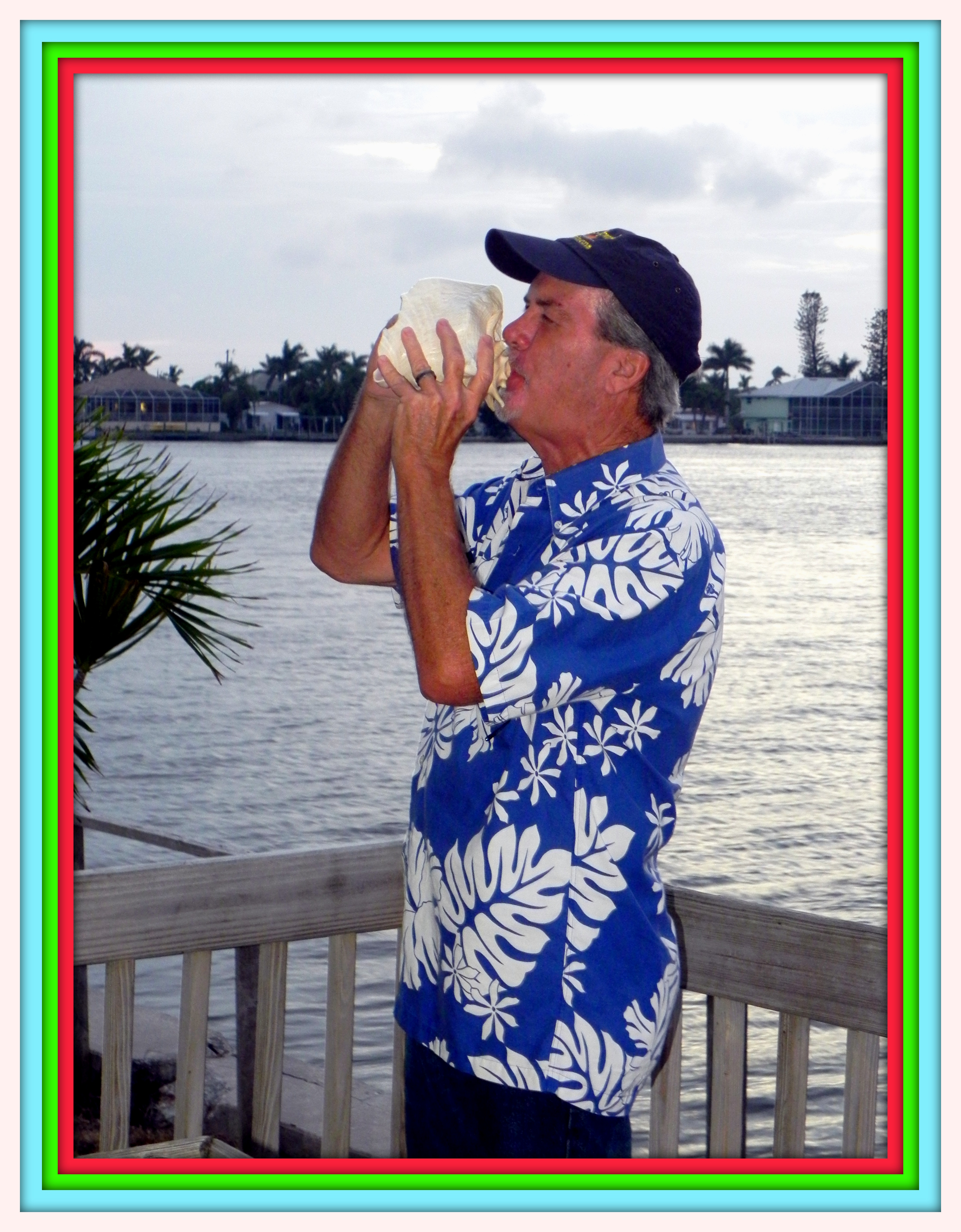 Author Robert N. Macomber sounds the conch at his annual Holiday Party at Bert's Pine Bay Gallery in Matlacha.